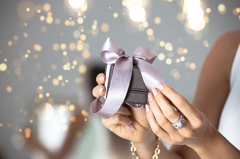 Close up of woman hands wearing large diamond ring and gold bracelet, holding small gift with ribbon with holiday lights in the background.