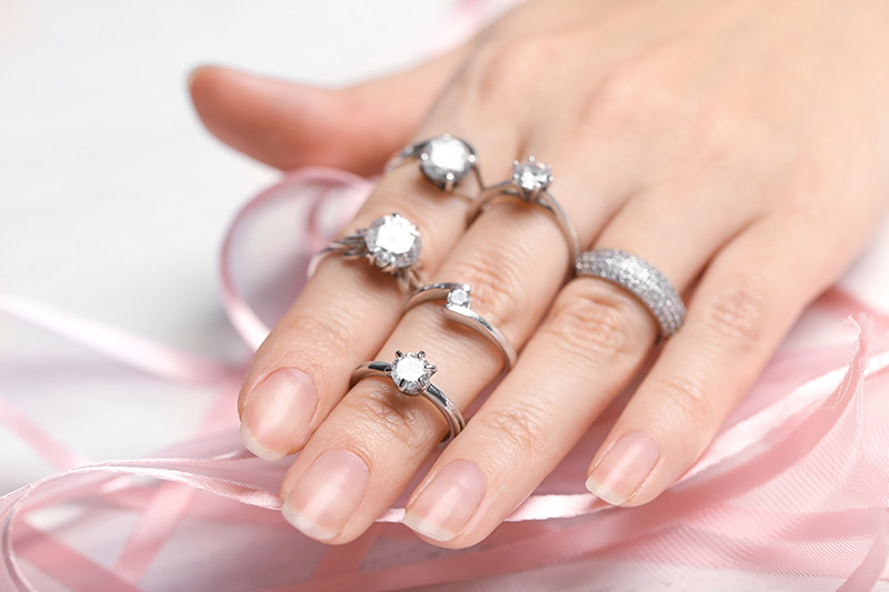 Woman wearing many different diamond engagement rings, closeup