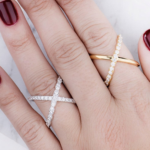 2 hearts on fire diamond rings on a young women's hands with red painted nail polish