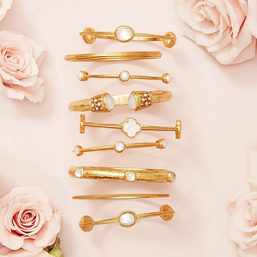 Juilie Vos gold plated bracelets and bangles on a light pink background surrounded by roses