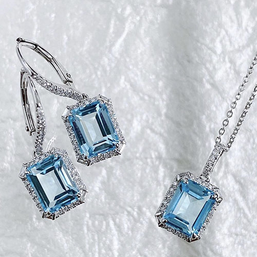 earring and necklace set made of white gold featuring blue topaz center stones surrounded by diamonds