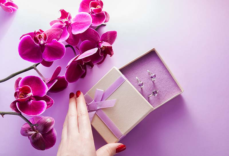women openeing a gift bow with white gold and gemstone jewelry with purple orchid flowers