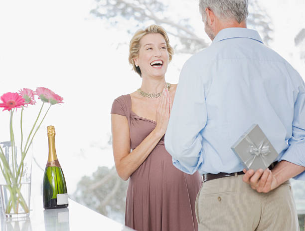 man gifting his wife diamond necklace and diamond earrings on their anniversary